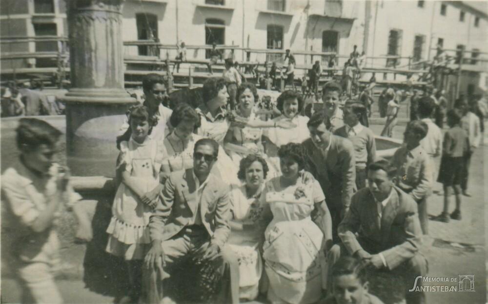 Mozas y mozos posando en el pilar de la plaza