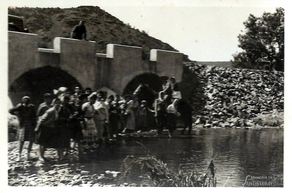 Grupo de gente posando bajo un puente